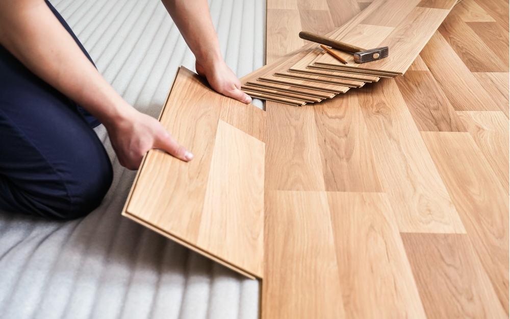 Installing,Laminated,Floor,,Detail,On,Man,Hands,Holding,Wooden,Tile,